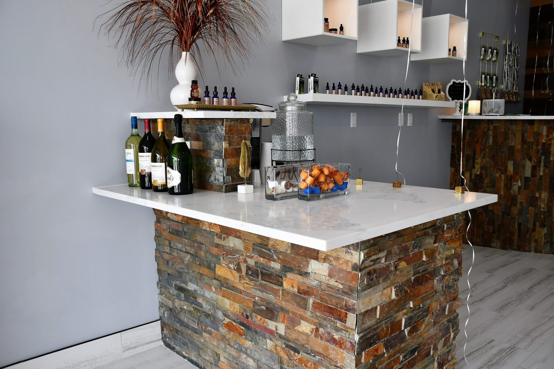 A small counter with wine, CBD oils, and refreshments.