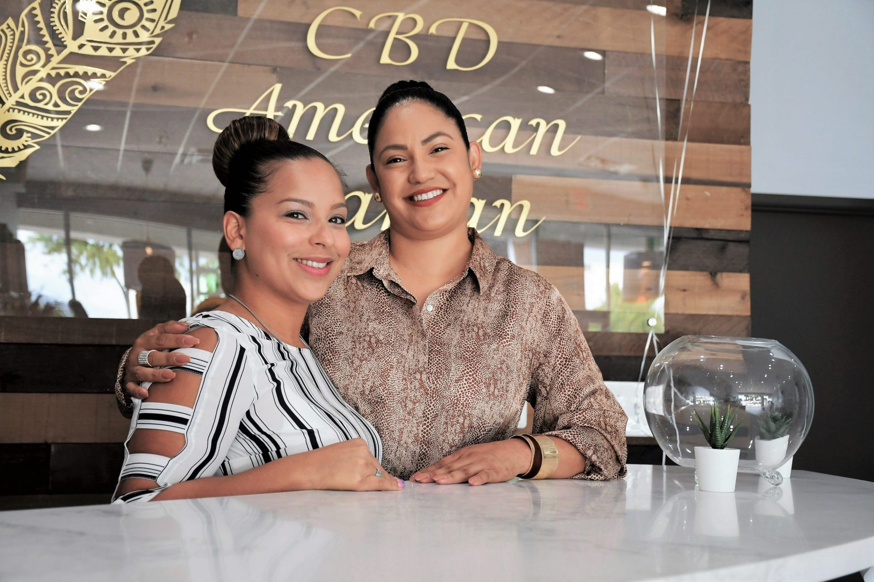 Two women posing at the front desk of CBD store.