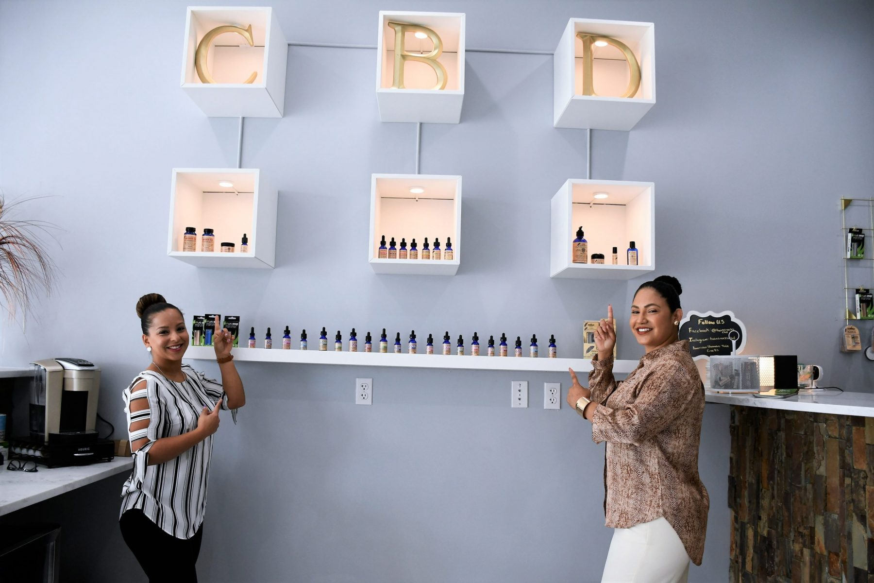 Two women are pointing to the selection of CBD oils available.