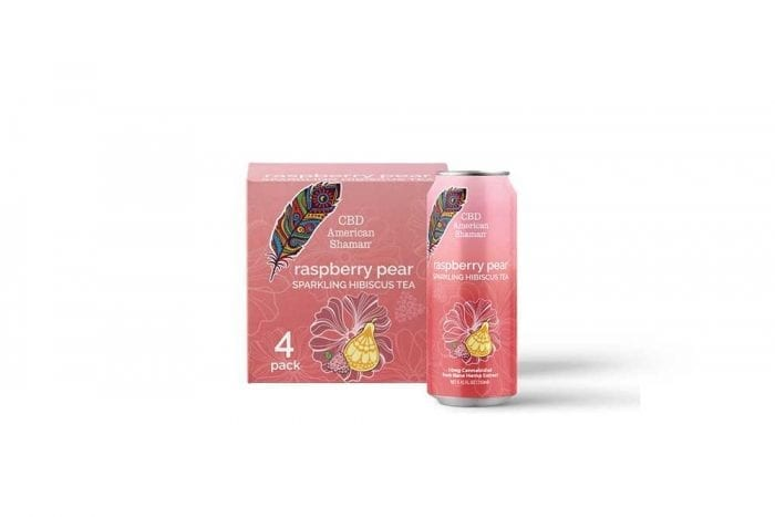 A pink can of raspberry tea, and a case of tea behind it.